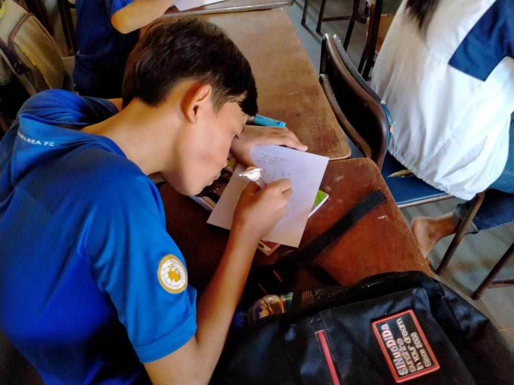 ノートを斜めにして書く子供